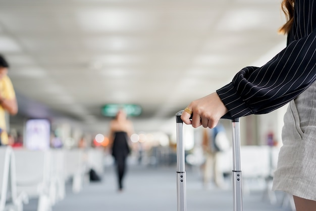 Mão de empresária tocando bolsa bagagem