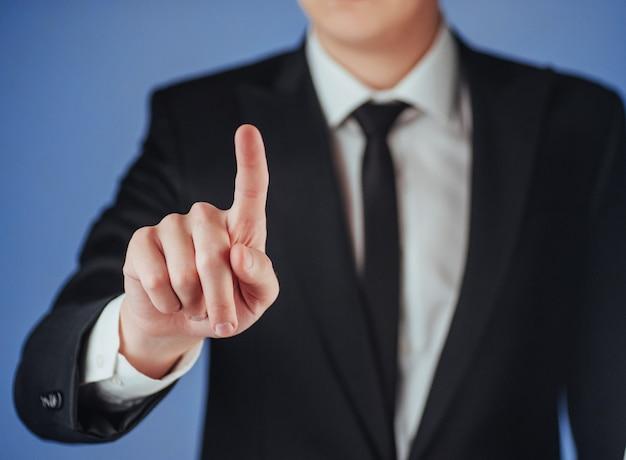 Mão de empresário, apontando no espaço vazio em fundo preto