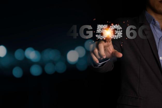 Mão de empresário, apontando o infográfico de sinal 5g com fundo preto e bokeh