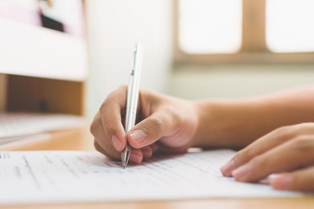 Mão de empresário, assinando o contrato de contrato de negócios de documento
