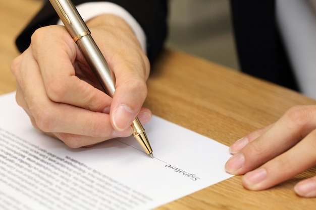 Mão de empresário, assinando um contrato de papel