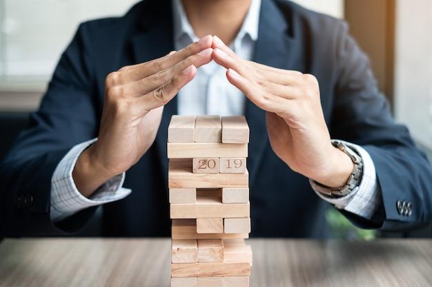 Mão de empresário cobrem o bloco de madeira na torre