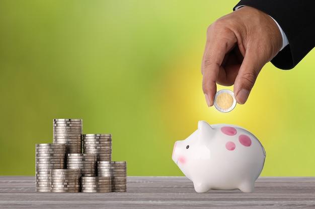 Mão de empresário colocando moedas no cofrinho com empilhamento de moedas na mesa de madeira