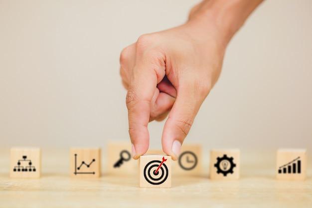 Mão de empresário colocando o bloco de cubo de madeira no topo com o alvo de ícone