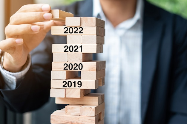 Mão de empresário colocando ou puxando o bloco de madeira na torre. conceitos de gestão de risco, resolução, estratégia, solução, objetivo, negócios e feriado de ano novo