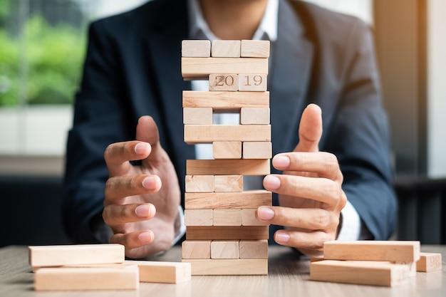Mão de empresário, colocando ou puxando o bloco de madeira no reboque