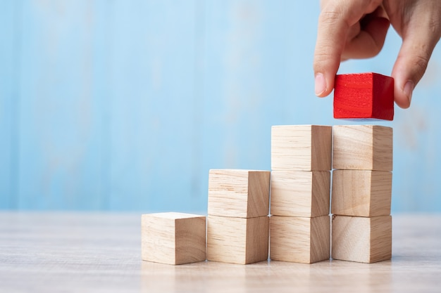 Mão de empresário, colocando ou puxando o bloco de madeira vermelho no edifício.