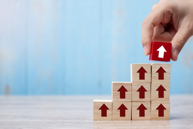Mão de empresário, colocando ou puxando o bloco vermelho com seta e crescimento seta para cima na mesa