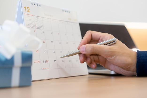 Mão de empresário com caneta escrevendo no calendário para nota ou fazer nomeação