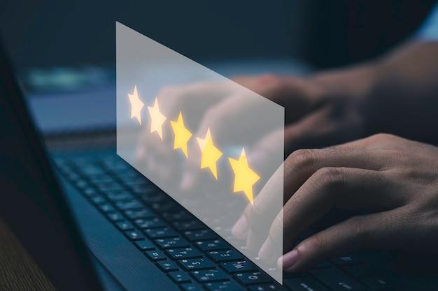 Mão de empresário com estrelas amarelas para digitar o teclado do computador portátil para fazer pesquisa de avaliação, conceito de satisfação do cliente.