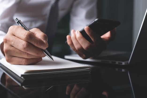 Mão de empresário com uma caneta escrevendo no caderno trabalhando no escritório
