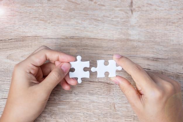 Mão de empresário, conectando a peça do quebra-cabeça casal