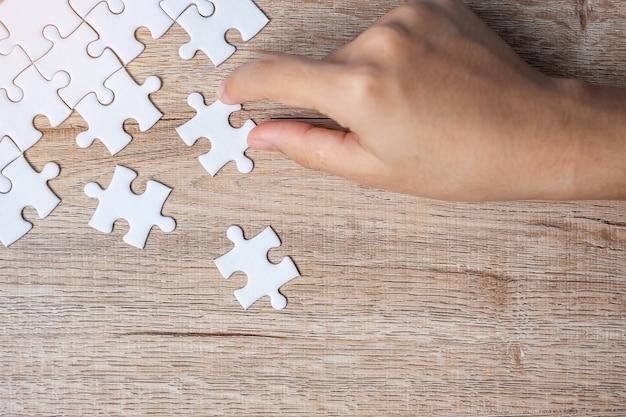 Mão de empresário, conectando a peça do quebra-cabeça