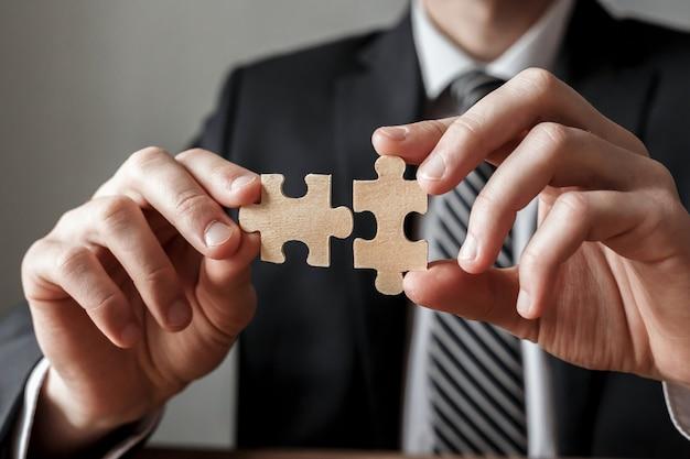 Mão de empresário, conectando o quebra-cabeça. conceito de soluções, sucesso e estratégia de negócios.