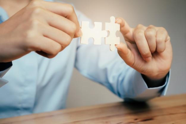Mão de empresário conectando o quebra-cabeça.