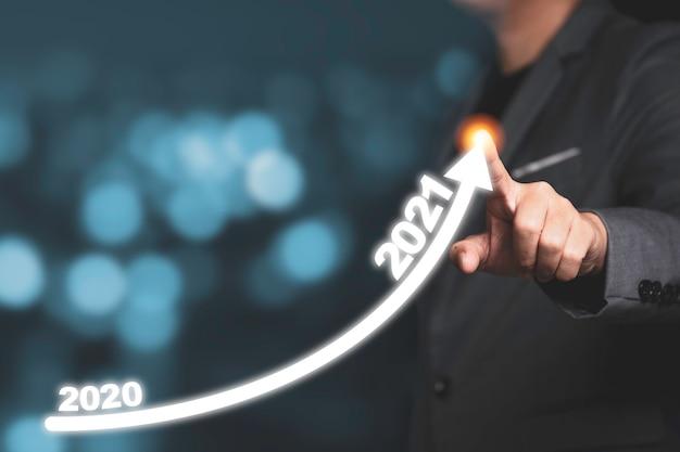 Mão de empresário desenhando a seta de tendência de aumento de 2020 a 2021. é o símbolo do conceito de crescimento do investimento empresarial.