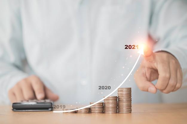 Mão de empresário desenho gráfico crescente virtual com empilhamento de moedas de dinheiro, lucro de investimento empresarial e crescimento de poupança de dividendos de depósito em 2021 conceito.