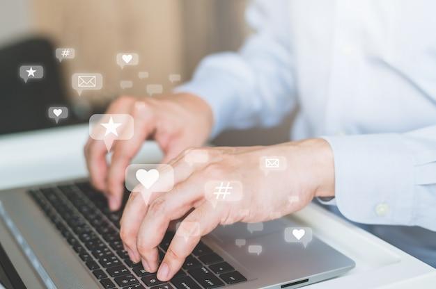 Mão de empresário digitando no teclado do laptop.