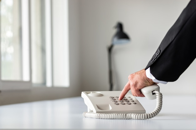 Mão de empresário discando um número de telefone usando o telefone fixo branco na mesa do escritório branco.