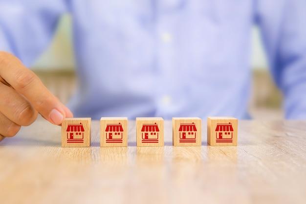 Mão de empresário escolhe blog de madeira com loja de ícones de marketing de franquia