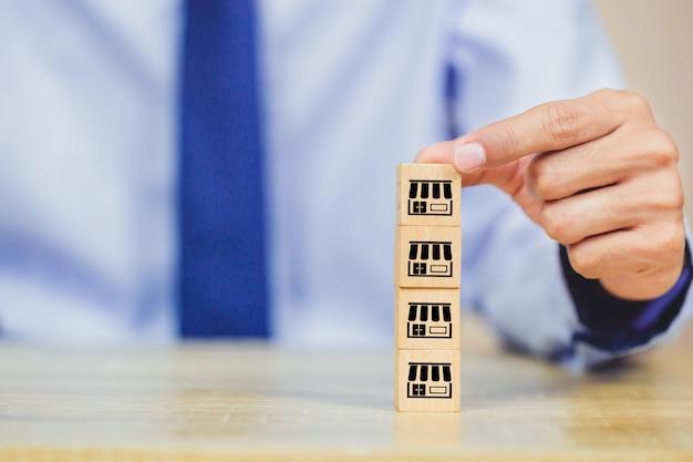 Mão de empresário escolher blog de madeira com marketing de franquia.