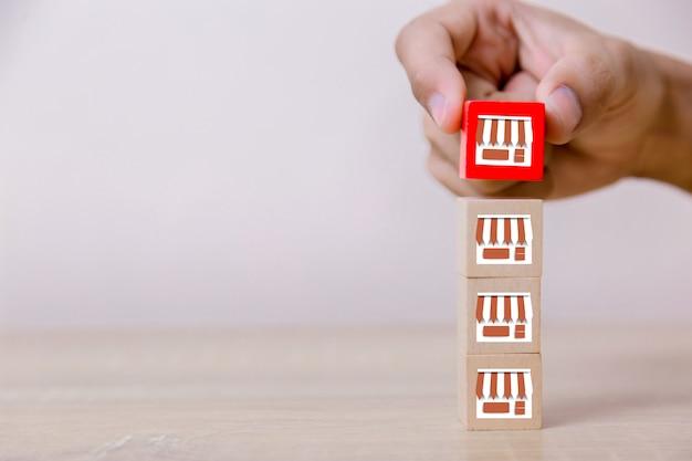 Mão de empresário escolher blog de madeira com marketing de franquia