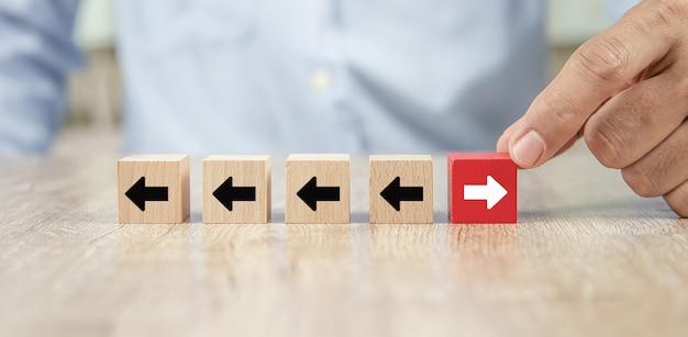 Mão de empresário escolher cubo brinquedo de madeira blog com ícones de cabeças de seta apontando para direções opostas.