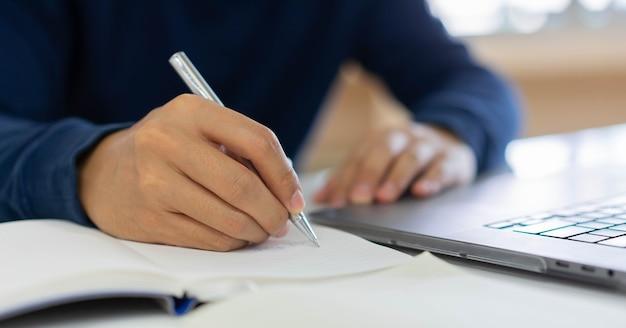 Mão de empresário escrevendo conteúdo ou algo no caderno com o uso de laptop