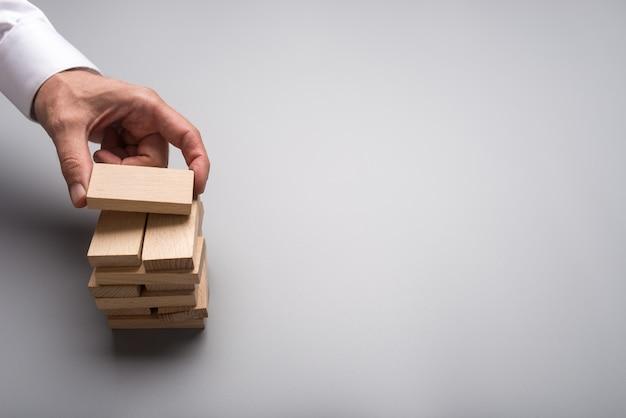 Mão de empresário fazendo uma pilha de pinos de madeira