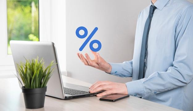Mão de empresário leva um ícone de símbolo de porcentagem. conceito de taxas financeiras e hipotecas de taxa de juros.