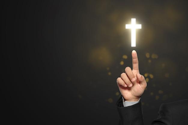 Mão de empresário mostrando cruz cristã com fundo preto