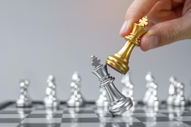 Mão de empresário movendo a figura do rei xadrez de ouro e enermy ou oponente do xeque-mate durante a competição do tabuleiro de xadrez.