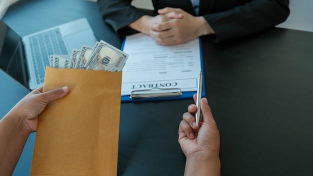 Mão de empresário oferece suborno de dinheiro em envelope para assinatura de um contrato de projeto empresarial, conceito de corrupção e antissuborno de funcionários do governo.