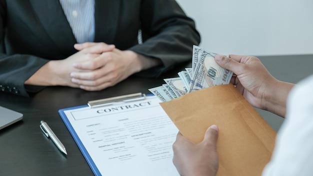 Mão de empresário oferece subornos dinheiro em envelope para assinar um contrato.