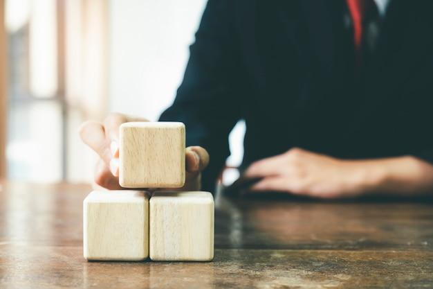 Mão de empresário, organizando a estratégia de negócios de bloco de madeira