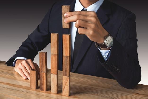 Mão de empresário organizando empilhamento desenvolvimento de blocos de madeira como degrau