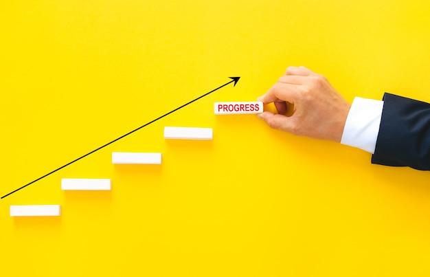 Mão de empresário organizando o empilhamento de blocos de madeira como escada de passo com seta de negócios de crescimento.