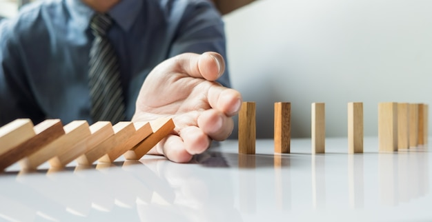 Mão de empresário pára dominó continuamente derrubado ou risco com copyspace