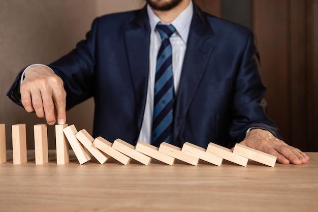Mão de empresário, parando de queda de madeira efeito dominó de contínuo derrubado ou risco, estratégia e conceito de intervenção bem-sucedida para negócios.