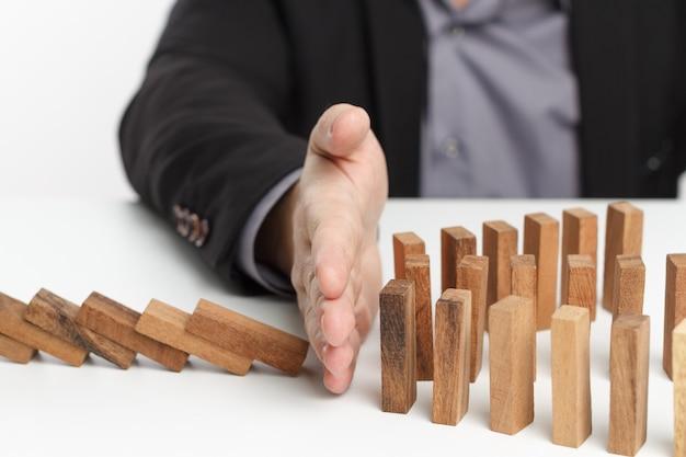 Mão de empresário parar risco ou inclinação contínua de dominó. estratégia nos negócios.