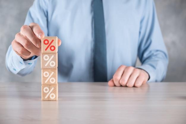Mão de empresário pega um bloco de cubo de madeira representando, mostrado o ícone do símbolo de porcentagem. conceito de taxas financeiras e hipotecas de taxa de juros.