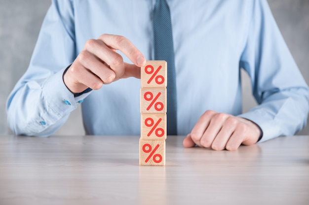 Mão de empresário pega um bloco de cubos de madeira mostrando o símbolo de porcentagem.