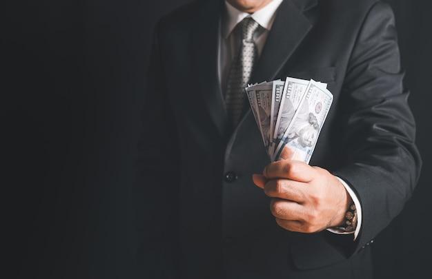 Mão de empresário pegando dinheiro, notas de dólar americano (usd) na parede preta, investimento, sucesso e conceitos de negócios lucrativos