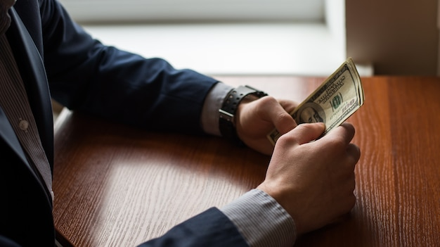 Mão de empresário pegando dinheiro