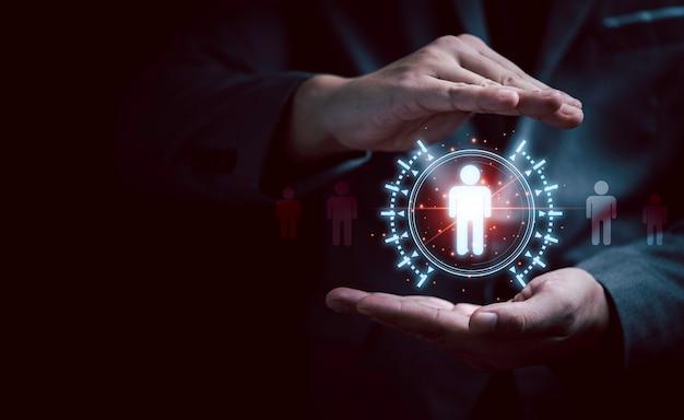 Mão de empresário protegendo o ícone humano virtual para o grupo de clientes em foco ou o conceito de recrutamento e desenvolvimento humano.