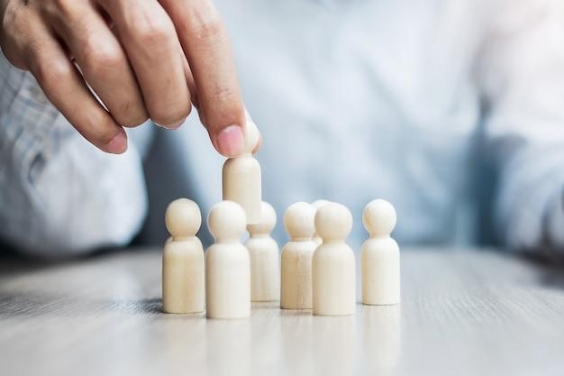Mão de empresário, puxando o homem líder de madeira da multidão de funcionários. pessoas, negócios, gestão de recursos humanos, recrutamento, trabalho em equipe, estratégia e liderança