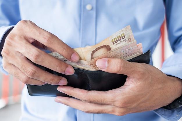 Mão de empresário segurando a pilha de notas de baht tailandês.