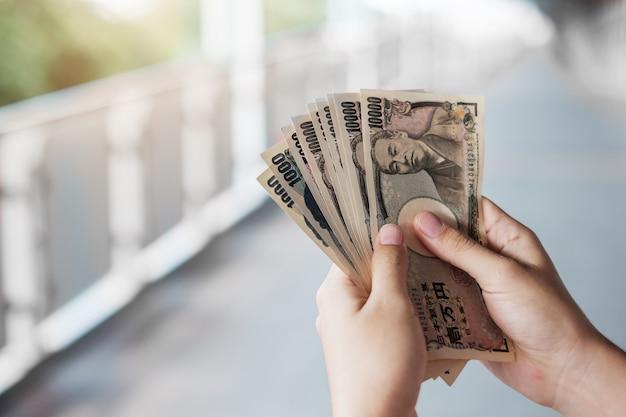 Mão de empresário segurando a pilha de notas de ienes japoneses. conceitos de negócios, dinheiro, investimento, finanças e pagamento
