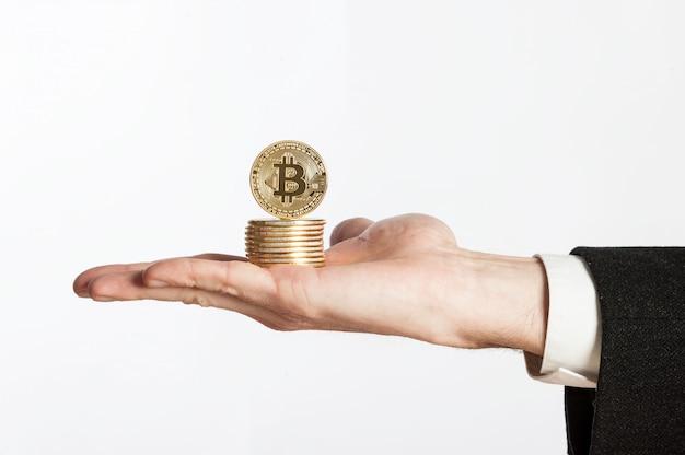 Mão de empresário segurando bitcoins em um branco