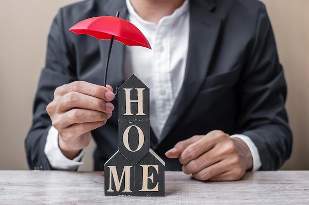 Mão de empresário segurando guarda-chuva vermelho modelo home de madeira no escritório mesa.